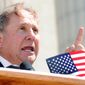 Conservative commentator Michael Reagan, son of former President Ronald Reagan, addresses about 400 people gathered for a Tea Party rally Tuesday morning, April 13, 2010, in front of the State Capitol in Jefferson City, Mo. Reagan likened liberals and progressives to termites who eat away at the foundation of American freedoms.(AP Photo/Kelley McCall)