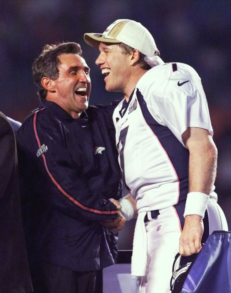 Denver Broncos quarterback John Elway, right, and head coach Mike Shanahan laugh on the victory stand following their 34-19 win over the Atlanta Falcons in Super Bowl XXXIII in Miami, Sunday, Jan. 31, 1999. (AP Photo/Amy Sancetta)