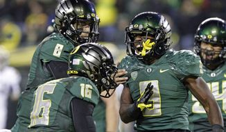 Oregon running back Byron Marshall, right, celebrates his touchdown with teammates Daryle Hawkins (16) and quarterback Marcus Mariota (8) during the second half of an NCAA college football game against UCLA in Eugene, Ore., Saturday, Oct. 26, 2013. Marshall ran for 133 yards and three touchdowns for a 42-14 victory. (AP Photo/Don Ryan)