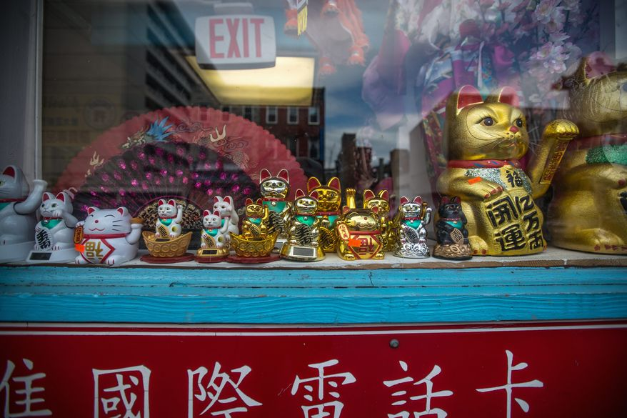 Chinese decorations line a businesses window along H street in the District. Challenges for Chinatown include the decline of small urban manufacturing and competition for mom-and-pop shops from national competitors. (Andrew S. Geraci/The Washington Times)