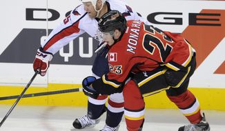 Washington Capitals' Jason Chimera, left, battles with Calgary Flames' Sean Monahan during second period NHL action in Calgary, Alberta Saturday, Oct. 26, 2013. (AP Photo/The Canadian Press, Larry MacDougal)