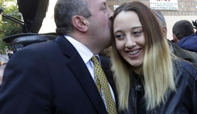 Georgian presidential candidate Georgy Margvelashvili (left) kisses his daughter Anna outside a polling station during during the presidential election on Sunday, Oct. 27, 2013, in Tbilisi, Georgia. (AP Photo/Georgy Abdaladze)