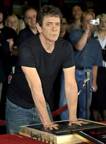 ** FILE ** Music icon Lou Reed has his hands imprinted as supporters cheer in the background during his induction ceremony for Hollywood's Rockwalk on June 24, 2003, in Los Angeles. (AP Photo/Ric Francis)