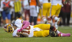Washington Redskins quarterback Robert Griffin III (10) lays on the turf after a hit by the Denver Broncos in the fourth quarter of an NFL football game, Sunday, Oct. 27, 2013, in Denver. Griffin left the game after the play. (AP Photo/Jack Dempsey)
