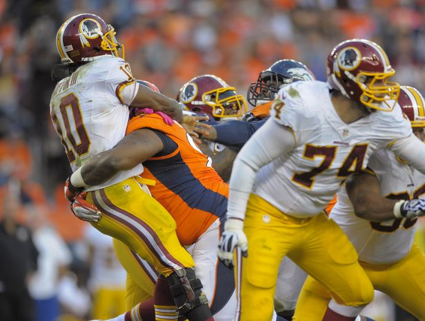 Washington Redskins quarterback Robert Griffin III (10) is hit by Denver Broncos defensive tackle Terrance Knighton (94) as he throws a pass in the fourth quarter of an NFL football game, Sunday, Oct. 27, 2013, in Denver.  Griffin was injured on the play and left the game. (AP Photo/Jack Dempsey)