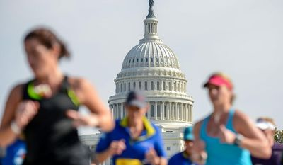 Runners make their way past the U.S. Capitol during the annual Marine Corps Marathon in Washington on Sunday, Oct. 27, 2013. (Andrew Harnik/The Washington Times)
