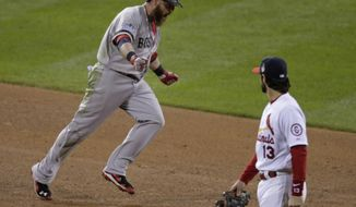 Boston Red Sox's Jonny Gomes reacts after hitting a three-run home run as he runs past St. Louis Cardinals' Matt Carpenter during the sixth inning of Game 4 of baseball's World Series Sunday, Oct. 27, 2013, in St. Louis. (AP Photo/Charlie Riedel)