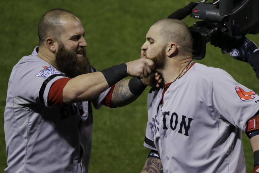 The Boston Red Sox's Mike Napoli (left) pulls teammate Jonny Gomes' beard after Gomes hit a three-run home run off St. Louis Cardinals relief pitcher Seth Maness during the sixth inning of Game 4 of baseball's World Series on Sunday, Oct. 27, 2013, in St. Louis. (AP Photo/Charlie Neibergall)
