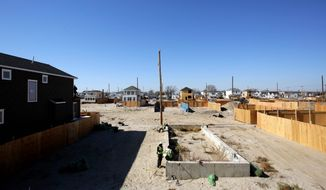 This Oct. 21, 2013, photo shows new home construction in the Breezy Point section of the Queens borough of New York. In the beachfront enclave of Breezy Point, new homes are beginning to rise after many months of inactivity on the sandy blocks where a year ago fire burned 130 houses and flooding destroyed another 220 during Superstorm Sandy. (AP Photo/Mark Lennihan)