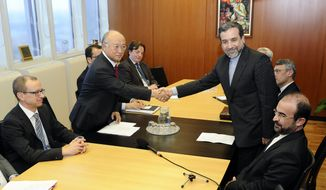 Iran's deputy Foreign Minister Abbas Araghchi, right, and Director General of the International Atomic Energy Agency, IAEA, Yukiya Amano shake hands next to IAEA deputy director general Tero Tapio Varjoranta, left, and Iran's Ambassador to the International Atomic Energy Agency, IAEA, Reza Najafi, right, prior a meeting at the International Center in Vienna, Austria on Monday, Oct. 28, 2013. The meeting was held before agency experts meet Iranian diplomats in a renewed push to probe suspicions that Tehran worked on nuclear arms. (AP Photo/Hans Punz)