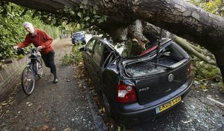 A car is crushed under a fallen tree as a man pushes a bicycle nearby following a storm, in Hornsey, north London, Monday, Oct. 28, 2013. A major storm with hurricane-force winds is lashing southern Britain, causing flooding and travel delays including the cancellation of roughly 130 flights at London's Heathrow Airport. (AP Photo/PA, Yui Mok)