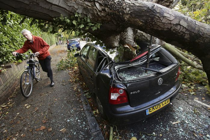 A car is crushed under a fallen tree as a man pushes a bicycle nearby following a storm, in Hornsey, north London, Monday, Oct. 28, 2013. A major storm with hurricane-force winds is lashing southern Britain, causing flooding