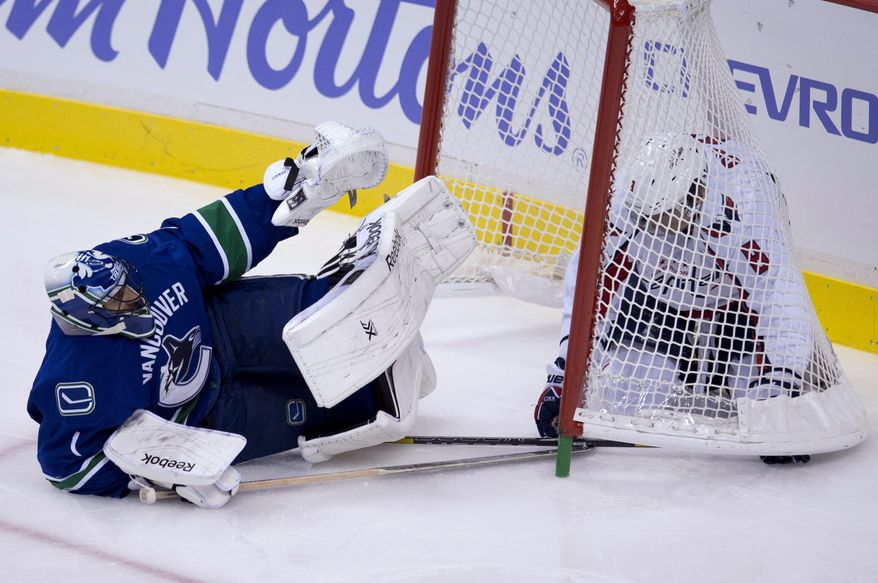 Washington Capitals right wing Alex Ovechkin, right, crashes into Vancouver Canucks goalie Roberto Luongo during the first period of NHL hockey action in Vancouver, British Columbia on Monday, Oct. 28, 2013. (AP Photo/The Canadian Press, Jonathan Hayward)