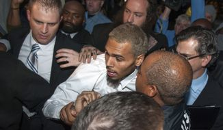 Singer Chris Brown is surrounded by bodyguards as he departs the H. Carl Moultriel courthouse Monday, Oct. 28, 2013, in Washington. A charge against the Grammy Award-winning R&B singer has been reduced to a misdemeanor and he was ordered released after his arrest Sunday following an altercation outside a Washington hotel. (AP Photo/Cliff Owen)