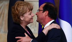 German Chancellor Angela Merkel and French President Francois Hollande embrace during a 2012 encounter. (credit: AP)
