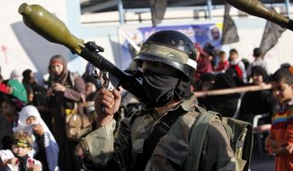 ** FILE ** Islamic Jihad militants hold rocket-propelled grenades during a rally marking the 26th anniversary of the movement's foundation and marking the 18th anniversary of the death of the group's leader, Fathi Shikaki, in the Rafah Refugee Camp in the southern Gaza Strip on Thursday, Oct. 24, 2013. Shikaki was gunned down in Malta by a man on a motorcycle in an attack widely attributed to Israel. (AP Photo/Adel Hana)
