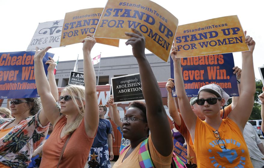 File - In this July 9, 2013 file photo, opponents and supporters of an abortion bill hold signs near a news conference outside the Texas Capitol, in Austin, Texas. New abortion restrictions passed by the Texas Legislature are unconstitutional and will not take effect as scheduled on Tuesday, a federal judge has ruled. (AP Photo/Eric Gay, File)