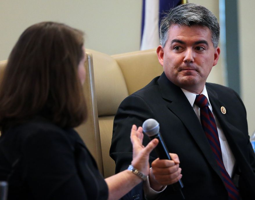 **FILE** After speaking, Rep. Cory Gardner, Colorado Republican, hands the microphone to Rep. Diana DeGette, Colorado Democrat, during a congressional luncheon and panel discussion sponsored by the Colorado Association of Commerce and Industry in Denver on Aug. 28, 2013. (Associated Press)