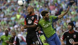 D.C. United's Kyle Porter, left, and Seattle Sounders's Brad Evans, right, head the ball in the second half of an MLS soccer match, Wednesday, July 3, 2013, in Seattle. The Sounders beat D.C. United, 2-0. (AP Photo/Ted S. Warren)