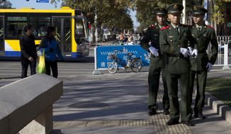 Chinese paramilitary police march on a sidewalk near the site of Monday's incident where a car plowed through a crowd before it crashed and burned in Beijing, China, Tuesday, Oct. 29, 2013. Police investigating the apparent car attack at Beijing's Forbidden City searched Tuesday for information on two ethnic Uighur minority suspects, a hotel employee said, a day after the incident which killed five people and injured 38.(AP Photo/Ng Han Guan)