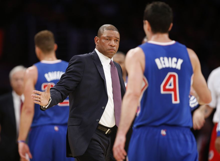 Los Angeles Clippers coach Doc Rivers, left, congratulates J.J. Redick, right, as he comes to the bench during a stop in play in the first half of an NBA basketball game against the Los Angeles Lakers in Los Angeles, Tuesday, Oct. 29, 2013. (AP Photo/Danny Moloshok)