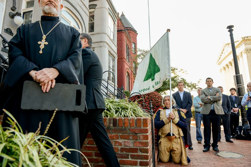 Dressed in colonial cloths, James Manship of Mt. Vernon, Va., Holds the Liberty Tree Flag as he listens to religious leaders speak before unveiling their depiction of the Ten Commandments again across the street from the Supreme Court after vandals pulled it over, Washington, D.C., Tuesday, October 29, 2013. (Andrew Harnik/The Washington Times)