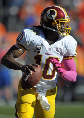 Washington Redskins quarterback Robert Griffin III scrambles against the Denver Broncos during an NFL football game Sunday, Oct. 27, 2013, in Denver. (AP Photo/Jack Dempsey)