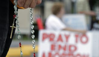 Phil Thiltrickett, an opponent of an abortion, holds a rosary as he prays outside a Planned Parenthood Clinic, Tuesday, Oct. 29, 2013, in San Antonio. (AP Photo/Eric Gay)