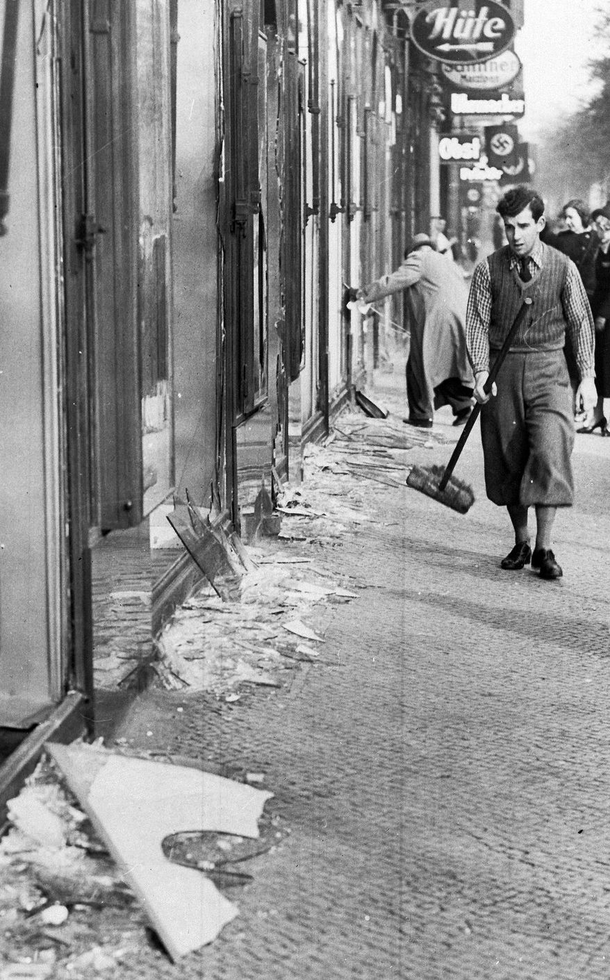 ** FILE ** A youth with a broom prepares to clear up the broken window glass from a Jewish shop in Berlin on Nov. 10, 1938, the day after the Kristallnacht rampage, when the Nazis set fire to hundreds of synagogues, looted thousands of Jewish businesses and attacked Jews in Germany and Austria. (Associated Press)