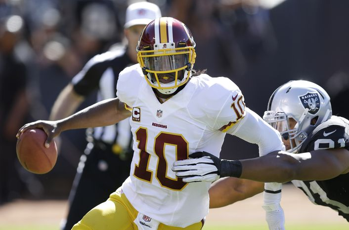 FILE - In this Sept. 29, 2013 file photo, Washington Redskins quarterback Robert Griffin III (10) runs from Oakland Raiders defensive end Jack Crawford (91) during the second quarter of an NFL football game in Oakland, Calif. It used to be the domain of soccer players, NBA forwards and the occasional punter.  Now, NFL quarterbacks are getting into the act. They are sports' newest floppers, putting their own tightly spiraled spin on the art of hamming it up to draw the ref's attention and a possible 15-yard penalty. (AP Photo/Ben Margot, File)