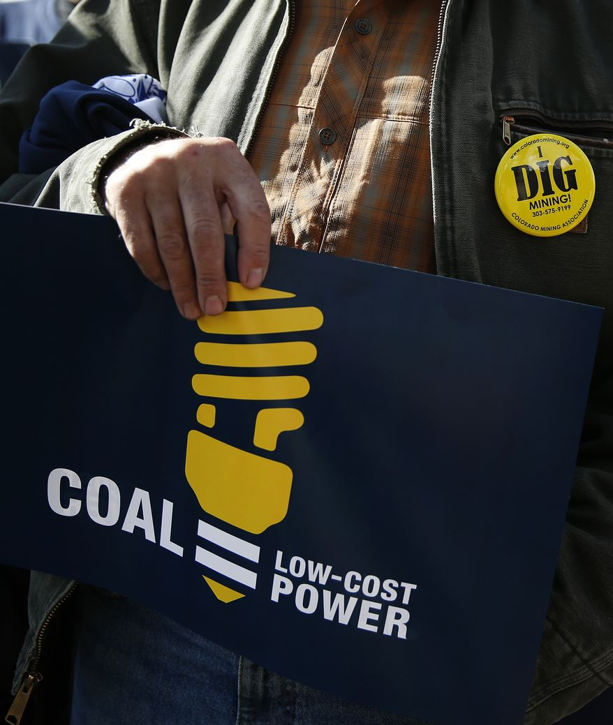 A protester carries a sign and wears a pin during a pro-coal rally in front of the state Capitol, in Denver, Wednesday Oct. 30, 2013. Various industry groups came together for the protest Wednesday, while nearby the Environmental Protection Agency held hearings on future rules to stem emissions from existing power plants, in one of 11 meetings being held across the country. (AP Photo/Brennan Linsley)