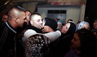 Released Palestinian prisoner Mohammed Sabbagh, center in white, is greeted by his relatives upon returning to his home in the West Bank refugee camp of Jenin after his release Wednesday, Oct. 30, 2013. Israel released 26 Palestinian prisoners, as part of a U.S.-brokered agreement that restarted peace talks with the Palestinians over the summer. It is the second of four planned releases of the longest-serving Palestinian prisoners held by Israel in the coming months. (AP Photo/Mohammed Ballas)