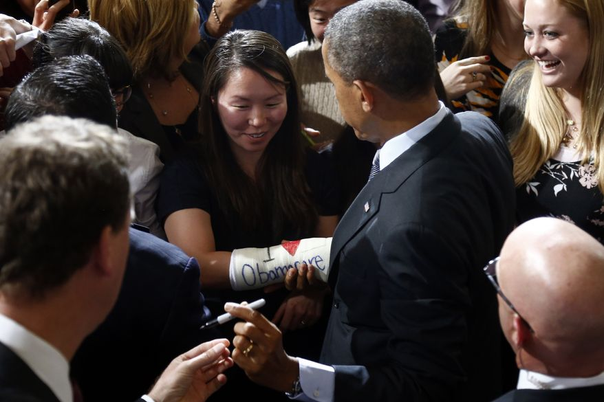 """President Barack Obama gets ready to sign the """"I Love Obamacare"""" cast of Cathey Park of Cambridge, Mass., after he spoke at Boston's historic Faneuil Hall about the federal health care law, Wednesday, Oct. 30, 2013. Faneuil Hall is where former Massachusetts Republican Gov. Mitt Romney, Obama's rival in the 2012 presidential election, signed the state's landmark health care law in 2006, with top Democrats standing by his side. (AP Photo/Charles Dharapak)"""