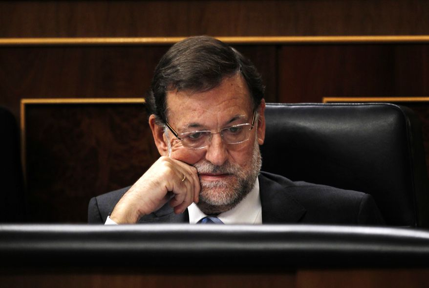 ** FILE ** Spain's Prime Minister Mariano Rajoy listens to a lawmaker at the Spanish parliament, in Madrid, Wednesday, Oct. 30, 2013. Speaking in parliament, Rajoy said Spain was taking the surveillance allegations seriously and that the head of Spain's intelligence services will address Parliament over allegations that Spain was a target for surveillance by the U.S. National Security Agency. (AP Photo/Francisco Seco)