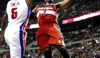 Washington Wizards guard John Wall (2) drives on Detroit Pistons forward Josh Smith (6) in the first half of an NBA basketball game in Auburn Hills, Mich., Wednesday, Oct. 30, 2013. (AP Photo/Paul Sancya)