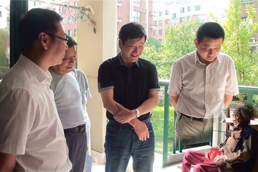 In a photo originally posted to a county government website, local officials purportedly visit a 100-year-old woman in Anhui province. 