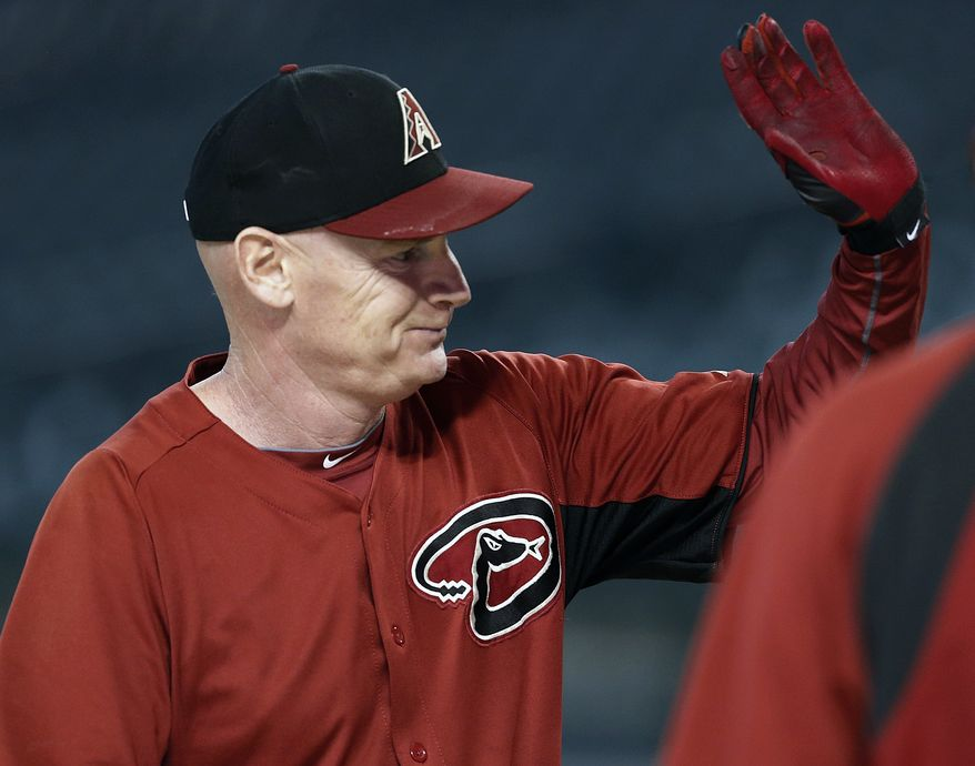 FILE - In this Aug. 26, 2013 file photo, Arizona Diamondbacks third base coach Matt Williams gets a high-five from players after he took batting practice prior to a baseball game against the San Diego Padres, in Phoenix. Williams is the new manager of the Washington Nationals. The Nationals will hold a news conference Friday, Nov. 1, 2013, to introduce Williams as the team's fifth manager since it moved to Washington from Montreal in 2005. He replaces Davey Johnson, who is retiring. (AP Photo/Ross D. Franklin, File)