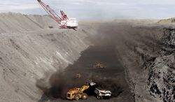 FILE - In this Oct. 9, 2013 file photo, a front end loader dumps coal into a hauler at a mining operation at the Navajo Mine in Fruitland, N.M. A company created by the Navajo Nation has signed off on the purchase of the coal mine in northwestern New Mexico. The $85 million deal with Australian-based BHP Billiton is expected to close on Dec. 1. The Navajo Mine is the sole provider of coal to the nearby Four Corners Power Plant (AP Photo/The Daily Times, Jon Austria, File)
