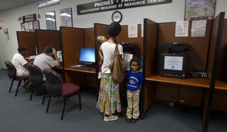 Shanieka Walford holds her sleeping daughter, Azanah Blount, and stands next to her son, Aminah Blount, as she faxes job applications from the WorkForce One office in Hollywood, Fla., on Friday, Sept. 7, 2012. (AP Photo/J. Pat Carter)