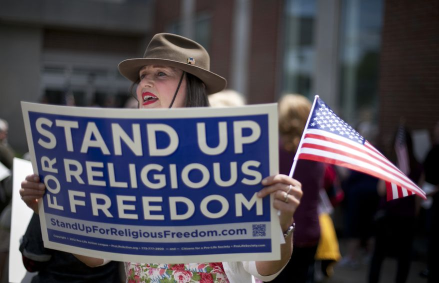 **FILE** Linda Lavoie, of West Bath, Maine, sings the Battle Hymn of the Republic during a rally to protest an upcoming federal mandate that most institutions and businesses provide insurance plans that cover artificial birth control on June 8, 2012, In Augusta, Maine. The guidelines from the Obama administration will go into effect in August. Opponents say requiring employers to provide those services through their health plans is a violation of religious freedom, despite promised exemptions and accommodations for religious institutions. (Associated Press)
