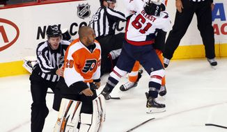 A linesman directs Philadelphia Flyers goalie Ray Emery, left, back towards the Flyers bench as Washington Capitals' Steve Olesky and Flyers' Vincent Lecavalier,  right, battle during a melee in the third period of an NHL hockey game Friday, Nov. 1, 2013, in Philadelphia. The Capital won 7-0. (AP Photo/Tom Mihalek)