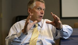 ** FILE ** This photo taken Tuesday, Oct. 15, 2013, shows Virginia Democratic gubernatorial candidate Terry McAuliffe gesturing during an interview in Richmond, Va. (AP Photo/Steve Helber)