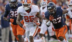 Clemson running back Roderick McDowell (25) heads to the end zone as Virginia safety Rijo Walker (27) and defensive end Mike Moore (32) follow during the first half of an NCAA college football game in Charlottesville, VA., Saturday, Nov. 2, 2013.   (AP Photo/Steve Helber)