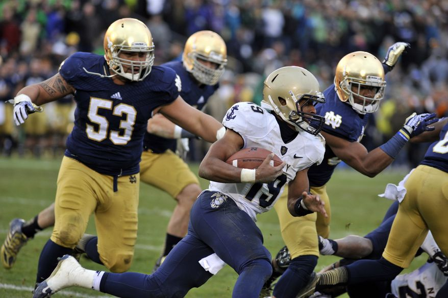 Navy quarterback Keenan Reynolds, center, heads around the end as Notre Dame's Justin Utopo, left, and Cole Luke, right, close in during the first half of an NCAA college football game, Saturday, Nov. 2, 2013, in South Bend, Ind. (AP Photo/Joe Raymond)