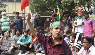 A Bangladeshi boy shouts slogans as he joins a rally with activists demanding the maximum penalty for war criminals in Dhaka, Bangladesh, on Sunday, Nov. 3, 2013. A special war crimes tribunal on Sunday sentenced to death two Bangladeshis now living abroad for crimes against humanity during the country's independence war against Pakistan in 1971. (AP Photo/Suvra Kanti Das)