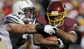 Washington Redskins running back Alfred Morris escpases the grip of San Diego Chargers linebacker Thomas Keiser during the first half of a NFL football game in Landover, Md., Sunday, Nov. 3, 2013. (AP Photo/Patrick Semansky)