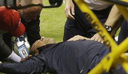 Houston Texans head coach Gary Kubiak gets medical attention after he collapsed while leaving the field at the end of the first half of an NFL football game against the Indianapolis Colts, Sunday, Nov. 3, 2013, in Houston. (AP Photo/Patric Schneider)