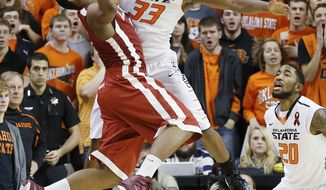 FILE- In this Feb. 16, 2013 file photo, Oklahoma State guard Marcus Smart (33) blocks a three-point shot attempt by Oklahoma guard Steven Pledger (2) with 18 seconds to go in overtime of an NCAA college basketball game in Stillwater, Okla. Smart is the only unanimous selection to The Associated Press' preseason All-America team, released Monday, Nov. 4, 2013. (AP Photo/Sue Ogrocki, File)
