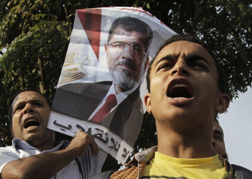 """Supporters of Egypt's ousted President Mohammed Morsi raise his poster with Arabic that reads, """"no to the coup,"""" during a protest in front of the supreme constitutional court in Cairo, Egypt, Monday, Nov. 4, 2013. (AP Photo/Amr Nabil)"""