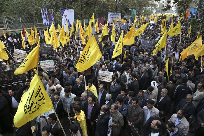 Iranian protesters hold flags during an annual anti-American demonstration in Tehran, Iran, Monday, Nov. 4, 2013. (AP Photo/Ebrahim Noroozi)